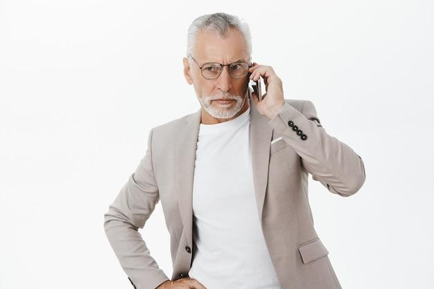 Poważny zaniepokojony stary biznesmen rozmawia przez telefon z zmartwioną miną
