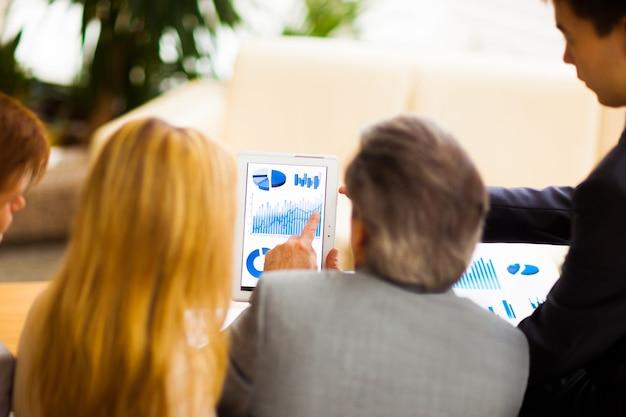 Poważny zespół biznesowy z dokumentami komputerowymi typu tablet pc prowadzący dyskusję w biurze