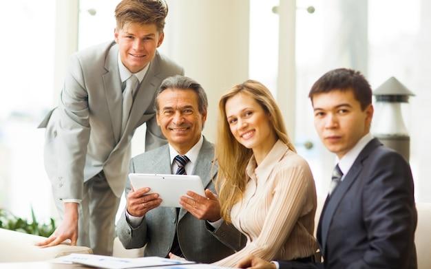 Poważny zespół biznesowy z komputerami typu tablet pc, dokumentami po dyskusji w biurze