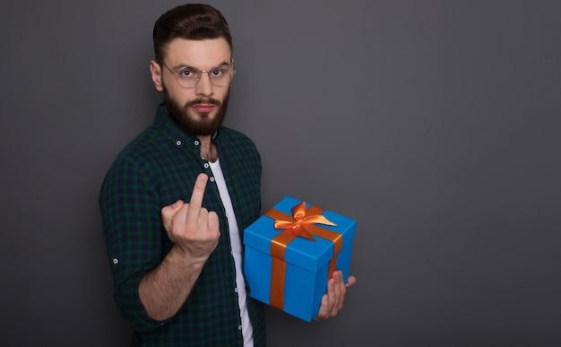Poważny zły brodaty mężczyzna z pudełkiem prezentowym pokazuje środkowy palec