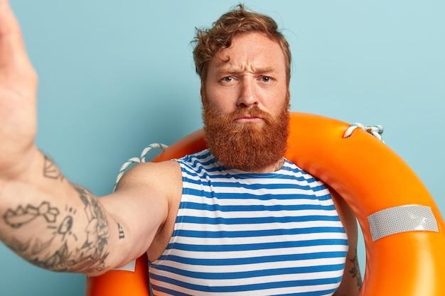 Poważny zły rudowłosy mężczyzna z grubą brodą robi selfie portret, nosi koło ratunkowe