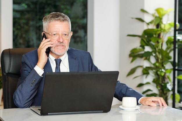 Poważny zły starszy przedsiębiorca pracuje na laptopie i rozmawia przez telefon z klientem