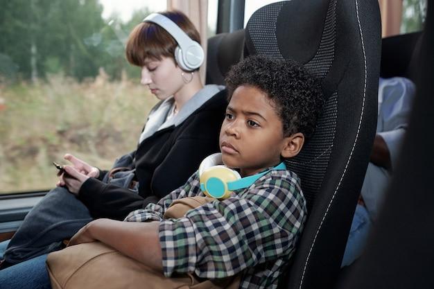 Poważny zmęczony czarny chłopak z kręconymi włosami obejmująca torbę podczas jazdy autobusem bez rodziców