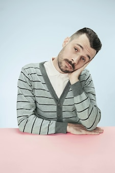 Poważny, znudzony i tępy biznesmen siedzi przy stole. portret w stylu minimalizmu