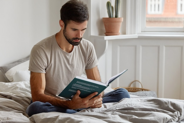 Poważny zrelaksowany, nieogolony mężczyzna trzyma książkę przed twarzą, ubrany w swobodną koszulkę, siedzi w pozie lotosu na łóżku