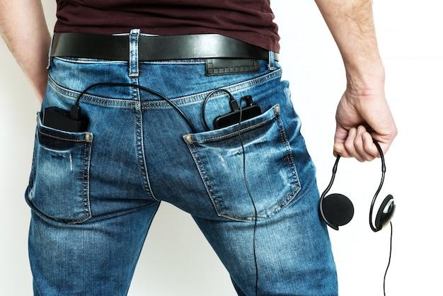 Power bank i smartfon w tylnej kieszeni dżinsów.