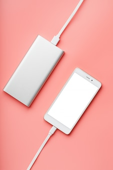 Power bank ładuje smartfon na różowym tle. uniwersalna zewnętrzna bateria dla gadżetów, wolnego miejsca i minimalistycznego składu.