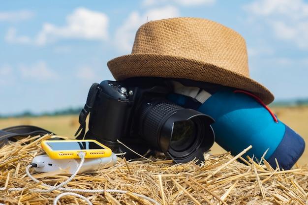 Power bank ładuje smartfon na tle aparatu fotograficznego z torbą i czapką na tle siana w naturze.