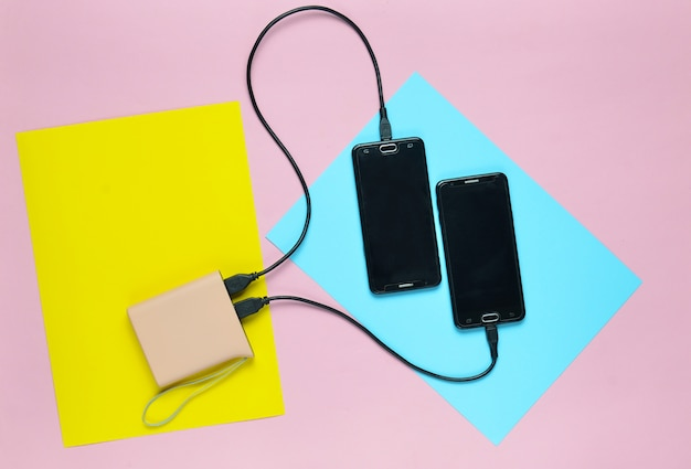 Power bank naładował dwa smartfony na kolorowej pastelowej powierzchni. nowoczesne gadżety. widok z góry. minimalizm