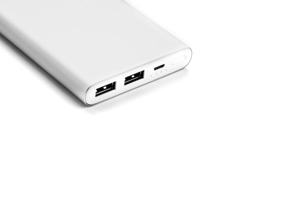 Powerbank do ładowania urządzeń mobilnych za pomocą kabla na białej powierzchni