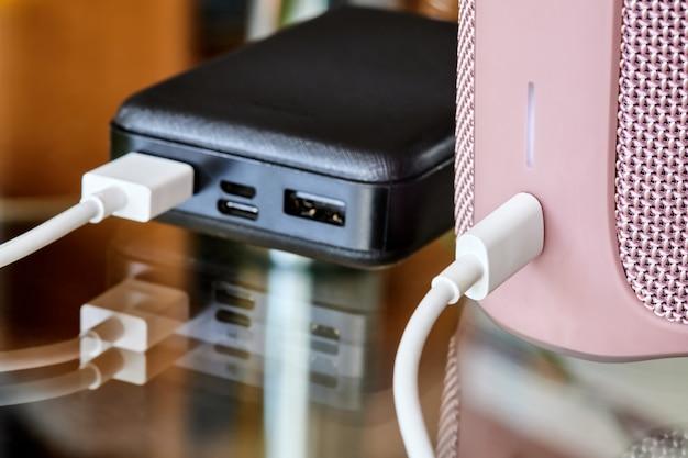 Powerbank ładuje przenośny głośnik za pomocą kabla usb na szklanej powierzchni