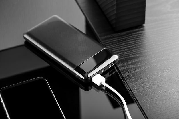 Powerbank ładuje smartfon na białym tle na czarnym tle