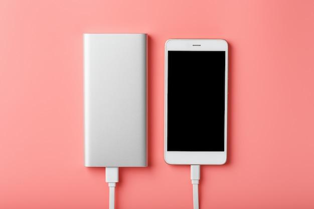 Powerbank ładuje smartfon na różowym tle. uniwersalna zewnętrzna bateria do gadżetów wolna przestrzeń i minimalistyczny skład.