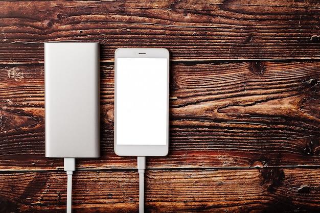 Powerbank ładuje smartphone na drewnianym tle. uniwersalna zewnętrzna bateria do gadżetów wolna przestrzeń i minimalistyczny skład.