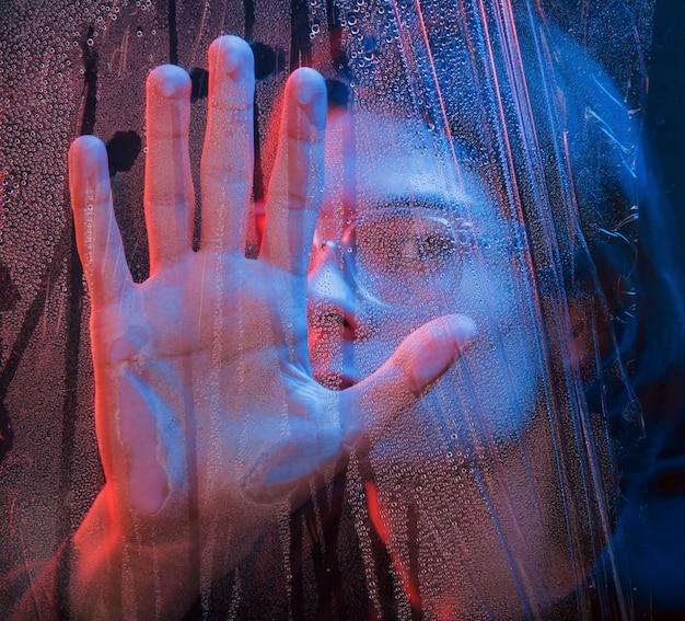 Powiedz cześć. studio strzałów w ciemnym studio z neonowym światłem. portret poważnego człowieka za mokrym szkłem