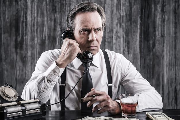 Powiedz mi wszystko, co wiesz! poważny starszy mężczyzna w koszuli i szelkach rozmawia przez staromodny telefon, siedząc przy stole i paląc cygaro