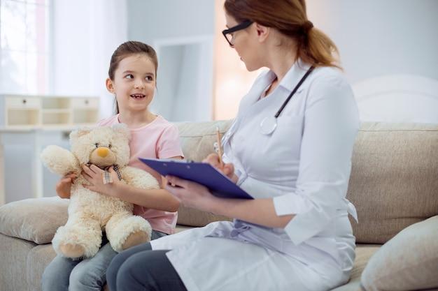 Powiedz mi wszystko. szczęśliwa wesoła dziewczyna rozmawia podczas gdy kobieta lekarz siedzi na kanapie i zapisuje objawy