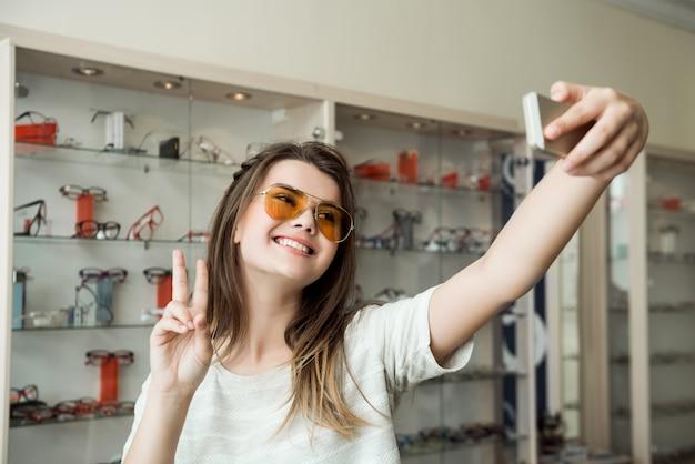 Powiedz ser do kamery portret atrakcyjnej kobiety na zakupy w sklepie optyka biorąc selfie i pokazując znak v podczas przymierzania okularów przeciwsłonecznych