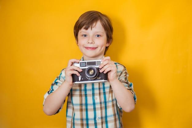 Powiedz ser. młody aktywny chłopiec robi zdjęcia aparatem retro, pozuje na żółtym tle, ma niesamowitą podróż, odkrywa nowe miejsca