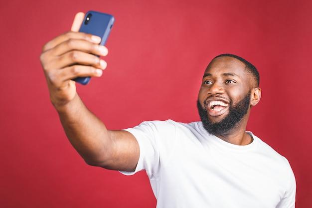 Powiedz ser. zamyka up młody piękny ciemnoskóry murzyn w przypadkowy ono uśmiecha się z zębami, trzyma smartphone, robi selfie fotografii.