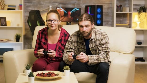Powiększ strzał pięknej młodej pary grających w gry wideo, siedząc na kanapie za pomocą kontrolerów.