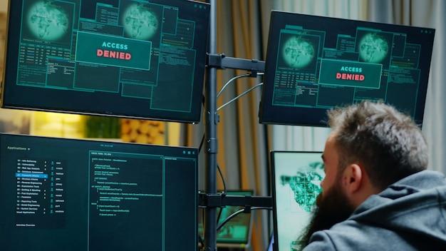 Powiększ ujęcie męskiego hakera próbującego włamać się do zapory sieciowej i odmowa dostępu.
