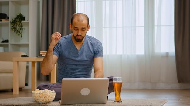 Powiększ ujęcie zły mężczyzna podczas rozmowy wideo podczas blokady koronawirusa pijącego piwo.