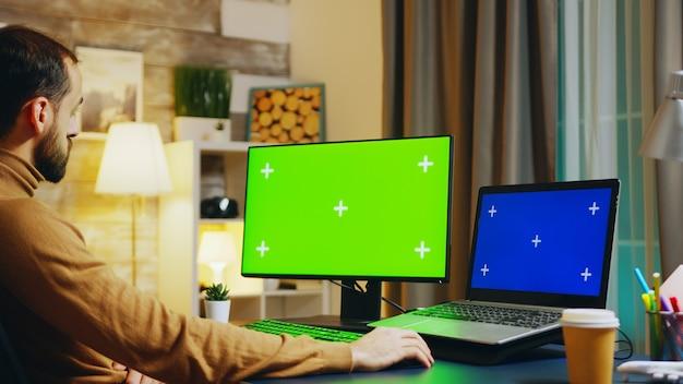 Powiększ zdjęcie inżyniera przy tym biurku pracującym na komputerze z zielonym ekranem. w biurze w nocy.