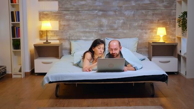 Powiększ zdjęcie pary w piżamie leżącej w łóżku za pomocą laptopa.