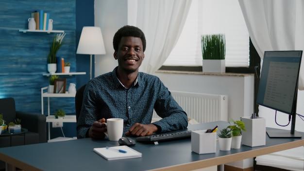Powiększ zdjęcie portretowe czarnoskórego mężczyzny z afryki, wolnego strzelca, uśmiechającego się do kamery, przystojnego młodego mężczyzny ...