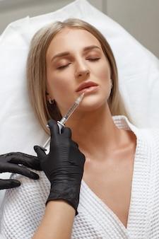 Powiększanie, korekta ust. portret białej kobiety podczas operacji wypełniania zmarszczek na twarzy. chirurgia plastyczna. młoda kobieta coraz zastrzyk kosmetyczny
