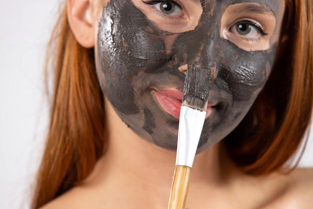 Powiększone zdjęcie kobieta nakłada na twarz czarną glinkową maskę pędzelkiem kosmetycznym