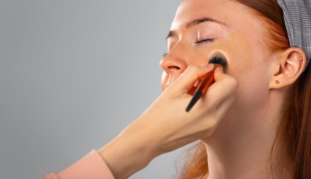 Powiększone zdjęcie kobiety z zamkniętymi oczami puder kosmetyczny nakłada się na twarz szarym pędzlem do makijażu