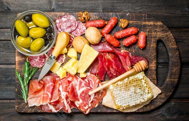 Powierzchnia antipasto. asortyment mięsnych przekąsek na desce z oliwkami i parmezanem. na drewnianej powierzchni.