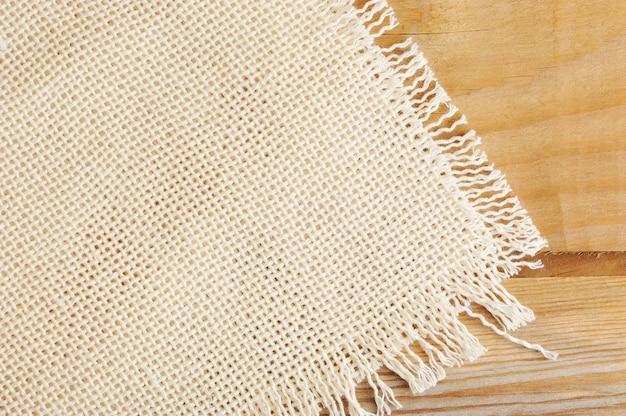 Powierzchnia białej grubej tkaniny lnianej na drewnianej desce