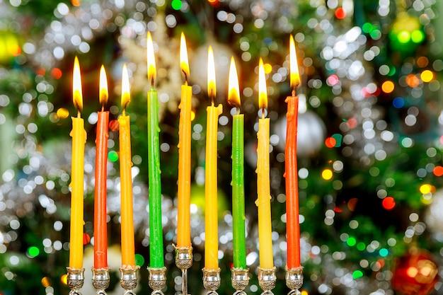 Powierzchnia chanuka z menorą i płonącymi świecami na błyszczącej powierzchni z rozmytymi światłami