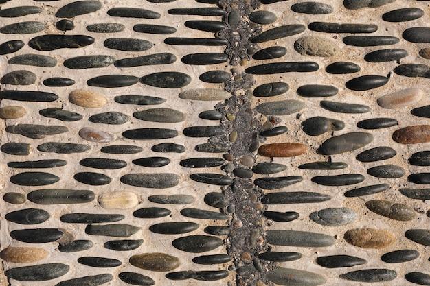 Powierzchnia chodnika jest pięknie wybrukowana kolorowymi kamykami. kolorowa kamienna ściana. chodnik z kamienia żwirowego. selektywna ostrość.