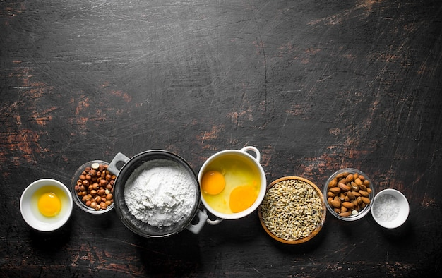 Powierzchnia do pieczenia. różne składniki na ciasto w miseczkach. na ciemnej rustykalnej powierzchni