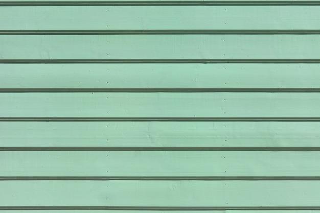 Powierzchnia drewnianych desek malowanych. zielonkawa akwamarynowa tekstura ściany z drewna na tło lub tapetę