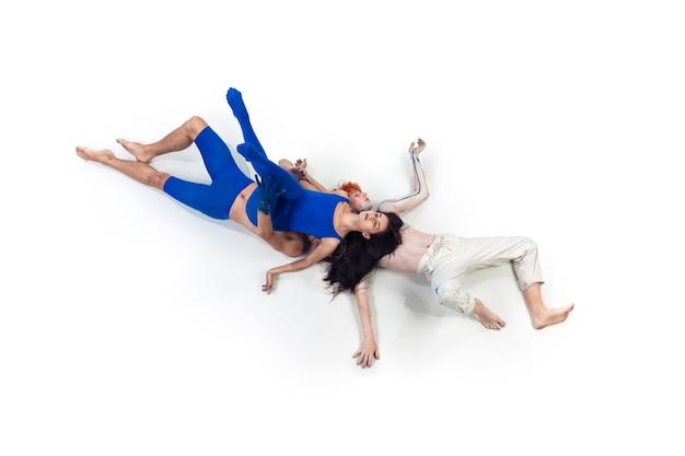 Powierzchnia. grupa tancerzy nowoczesnych, art contemp dance, niebiesko-białe połączenie emocji. elastyczność i gracja w ruchu i akcji na białym tle studia. moda i uroda, koncepcja grafiki.