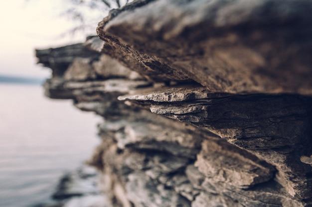 Powierzchnia kamiennego muru. czarny kamień tło. tekstura skały. tło stos skały.
