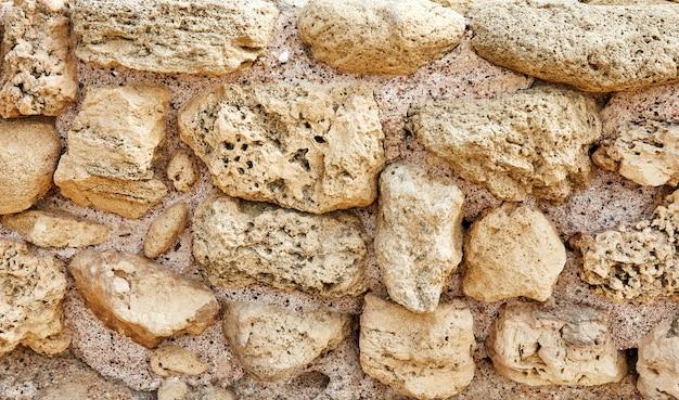 Powierzchnia kamiennej ściany zamku wykonana z kamieni o różnych kształtach, rozmiarach i fakturach