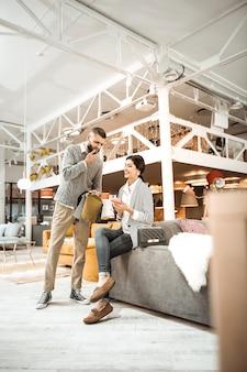 Powierzchnia kanapy. przemyślany wysoki mężczyzna drapie się po brodzie, myśląc o meblach i konsultując się z żoną