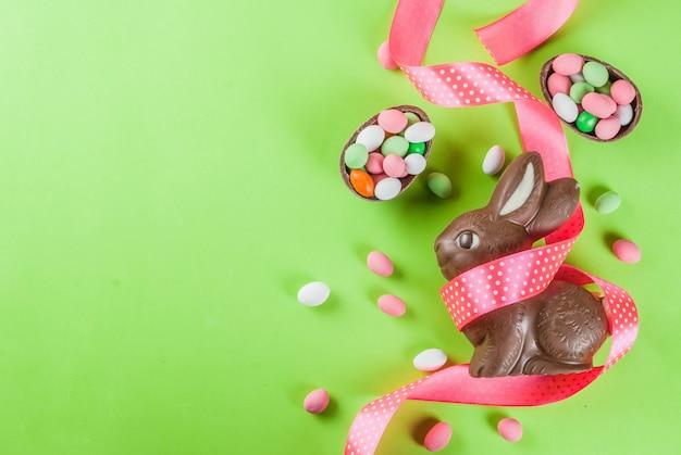Powierzchnia kartki wielkanocnej, z czekoladowym króliczkiem wielkanocnym, cukierkami, jajkami przepiórczymi i świątecznym wstążką, kopia przestrzeń widok z góry