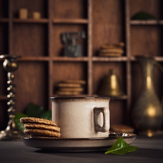 Powierzchnia kawiarni z brązową filiżanką kawy i holenderskimi tradycyjnymi ciasteczkami stroopwafels. stonowany styl retro