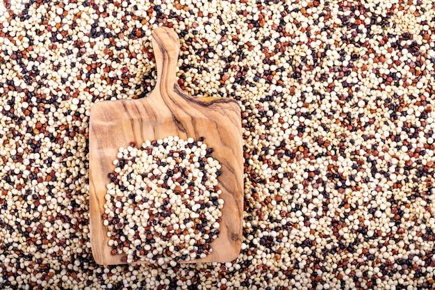Powierzchnia komosy ryżowej w kolorze czerwonym, białym i brązowym drewnianą łyżką. widok z góry. wolne miejsce na kopię.