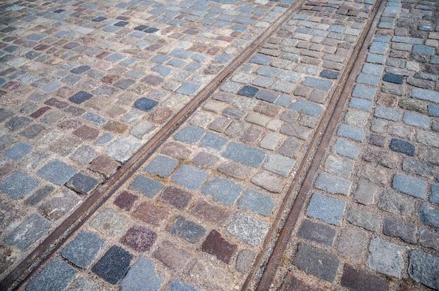 Powierzchnia kostki brukowej ze starymi zardzewiałymi szynami tramwajowymi