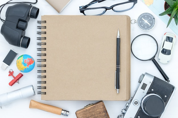 Powierzchnia podróżna z notatnikiem i ołówkiem pośrodku i akcesoriami podróżnymi dookoła