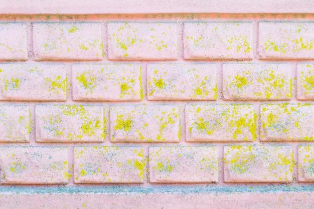 Powierzchnia ściany. różowa ściana pokryta pięknym mchem. stary ceglany płot pomalowany na różowo