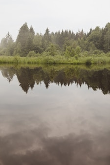 Powierzchnia spokojnej wody z odbiciem zachmurzonego nieba